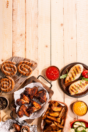 High Angle View of Grilled Meats and Vegetables with Sauces on Wooden Table Surface with Copy Space