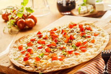 pancetta cubetti: Fiamma alla griglia tradizionale pizza alsaziana francese condita con mozzarella, prosciutto o pancetta a cubetti, cipolla ed erbe fresche in una cucina rustica visti basso angolo