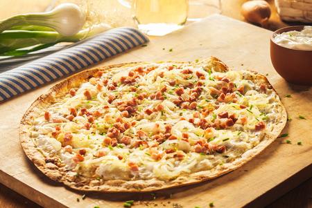 신선한 재료로 둘러싸인 나무 커팅 보드에 소박한 얇은 껍질 프랑스 피자 닫습니다
