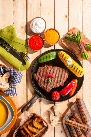 rump steak: High Angle View of Barbequed Meal Featuring Grilled Steak, Sausage, and Vegetables Served with Dips and Sides on Wooden Picnic Table Stock Photo
