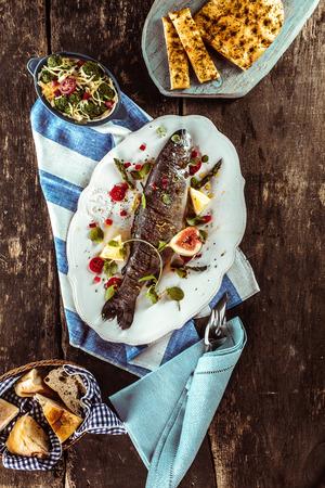 fish: Vista de �ngulo alto de la parrilla y adornado Pescado entero en la tabla de madera, rodeado de otros platos y servilletas de lino