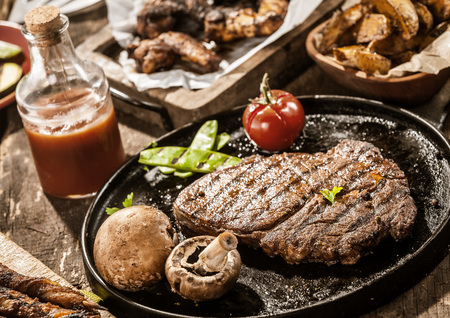 buffet: Rustic country meal of grilled ribe eye beef steak with mushrooms and tomato served with homemade ketchup and assorted barbecued meats on a summer picnic Stock Photo