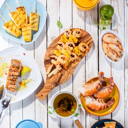 prawn skewers: High Angle View of Grilled Fruit and Seafood Dishes Arranged on White Wooden Table Surface