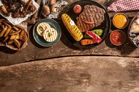 Hoog standpunt van de Maaltijd van gegrilde biefstuk, kip en groenten verspreid op rustieke houten tafel op Barbeque Party Stockfoto