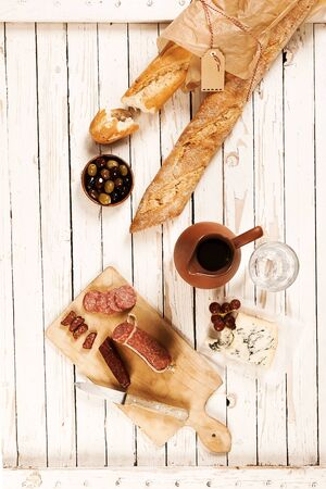 food and wine: Brown paper bag of crispy fresh baguettes with spicy sausage and salami, olives and cheese served on a wooden picnic table with a jug of red wine, overhead view