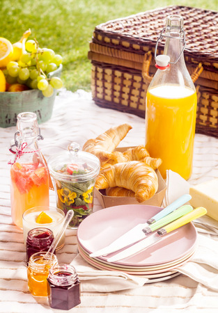 pic nic: Fruit juice, croissants and fresh fruit for a summer picnic laid out on a blanket on a green lawn with a rustic wicker hamper