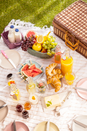 pic nic: Healthy tropical summer picnic with fresh organic fruit, milk, fruit juice, croissants, butter, jam empty plates and a hamper laid out on a blanket on the grass