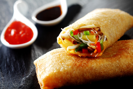 Close Up of Crispy Fried Vegetable Spring Rolls Stacked on Dark Textured Surface with Chili and Soy Sauces in Background Stock Photo
