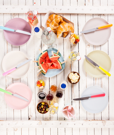 pic nic: Summer lunch served on a wooden picnic table outdoors with croissants, olives, preserves, butter, watermelon and fruit juice between two rows of empty plates with knives, overhead view