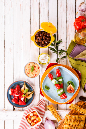 top angle view: High Angle View of Prepared Colorful Mediterranean Meal Appetizers Spread Out on Painted White Wooden Picnic Table with Bright Plates and Copy Space