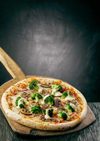 long handled: Tasty broccoli and mushroom pizza with a thick crust topped with melted mozzarella and served on a long handled wooden board in a pizzeria, with background copyspace Stock Photo