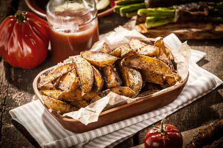 accompaniment: Delicious vegetarian cuisine with a platter of spicy potato wedges served with fresh tomato juice for a tasty snack or accompaniment to a summer picnic