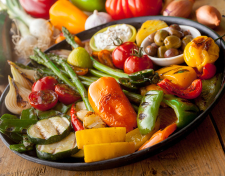 bounty: Bounty of Grilled Colorful Vegetables and Olives on Cast Iron Pan Resting on Wooden Table