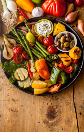 High Angle View of Bounty of Colorful Grilled Vegetables and Olives on Cast Iron Pan Resting on Wooden Table Surface with Copy Space in Foreground