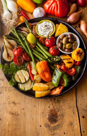 bounty: Vista elevada del Bounty de verduras y aceitunas a la plancha de hierro fundido de colores sobre Pan de descanso en la tabla de madera de superficie con espacio de copia en primer plano Foto de archivo