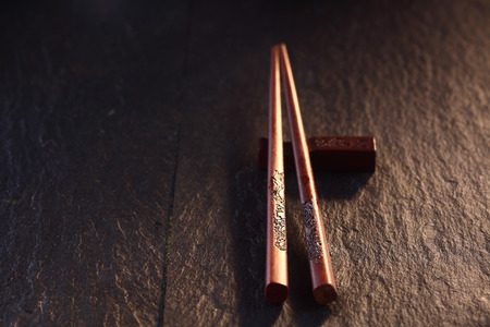 chop sticks: Close Up of Decorative Chop Sticks Resting on Rest on Wooden Table Surface in Warm Mood Lighting with Copy Space