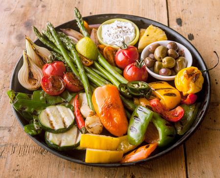 bounty: High Angle View of Bounty of Colorful Grilled Vegetables and Olives Served on Cast Iron Pan and Resting on Wooden Table Surface