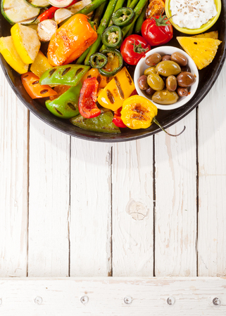 bounty: High Angle View of Colorful Grilled Vegetable Bounty on Cast Iron Pan with Olives and Dip Resting on White Painted Wooden Picnic Table with Copy Space Stock Photo
