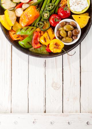 bounty: Vista elevada de colorido Bounty vegetales a la parrilla en sartén de hierro fundido con aceitunas y Dip Descansando en blanco pintado Mesa de jardín de madera con el espacio de la copia