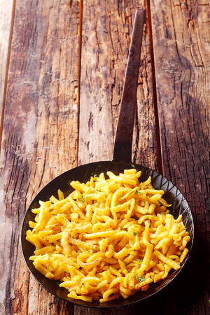 accompaniment: Golden Bavarian spaetzle, or boiled egg noodles, with copyspace served on an old textured wooden counter top for a tasty snack or accompaniment to a meal Stock Photo