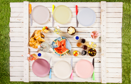 picnic table: Overhead view of food and empty plates on a summer picnic table outdoors on the grass with croissants, watermelon, olives, fruit salad, juice and jam