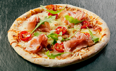 pizza base: Delicious homemade pizza with a thick base or crust topped with mozzarella cheese, tomato paste, ham and fresh rocket leaves on a black counter top