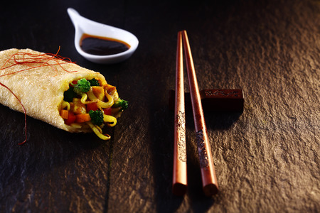 Close Up of Decorative Chop Sticks and Spring Roll on Textured Wooden Table Surface in Warm Mood Lighting Imagens