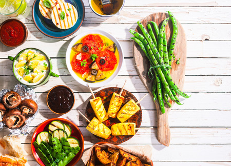 buffet: High Angle View of Vegetarian Mediterranean Meal of Grilled Fruit and Vegetables Spread Out on White Wooden Picnic Table with Copy Space Stock Photo