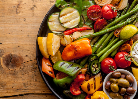 grill: High Angle View of Bounty of Colorful Grilled Vegetables and Olives Served on Cast Iron Pan and Resting on Wooden Table Surface with Copy Space
