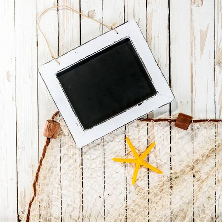 themed: Blank vintage school slate on a nautical background with a starfish and fishing net on weathered white wood boards