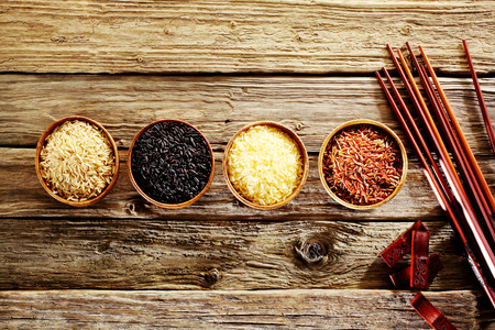 Four bowls of different varieties of rice with basmati, wild rice, long grain and red rice with a set of bamboo chopsticks depicting Asian cuisine on a rustic weathered wood background