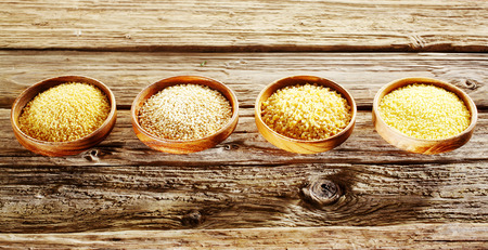 millet: Assortment of healthy grains and seeds for use as cooking ingredients with crushed wheat in the form of couscous and bulgur, millet and quinoa, rich in starch and protein on a rustic wood background Stock Photo