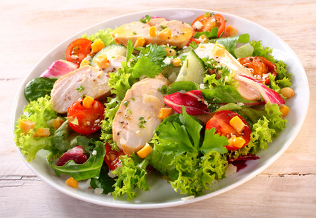 vegetable salad: Close up Healthy Fresh Chicken Garden Salad on a White Plate, Served on a Wooden Table. Stock Photo