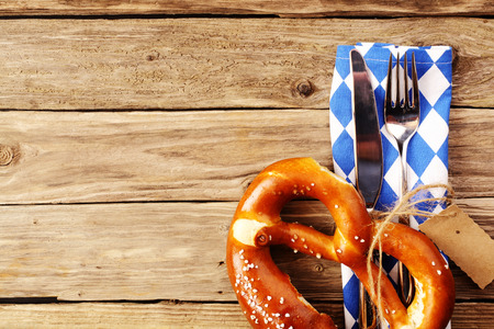 eating utensils: Eating utensils with a Bavarian pretzel and a white and blue napkin in Bavarian colors on a wooden table in a tavern, conceptual of Oktoberfest