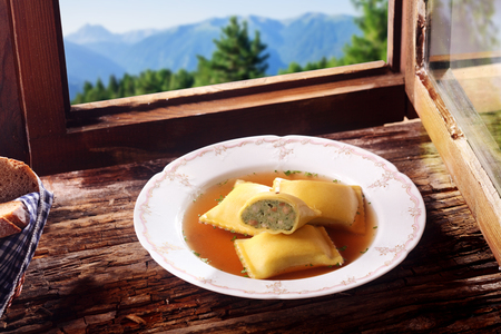 wiesn: German Stuffed ravioli pasta squares in a savory sauce cut through to reveal the vegetable stuffing and served on a rustic wooden windowsill overlooking the Bavarian alps Stock Photo