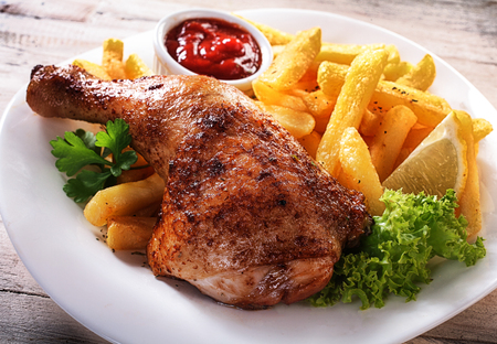 Close up Gourmet Tender Juicy Chicken and Fries Dish on a White Plate with Fresh Lettuce, Lemon and Sauce.