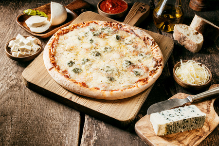 Fresh ingredients for a four cheeses Italian pizza laid out in individual bowls on a rustic wooden kitchen counter around a baked pizza with tomato paste and herbs and a melted cheese topping