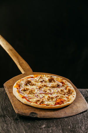 long handled: Flame grilled traditional Italian pizza served on a long handled rustic wooden board in a pizzeria or restaurant with copyspace over a dark background Stock Photo