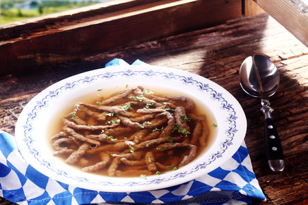 speciality: Savory liver spaetzle garnished with herbs, a speciality pasta made by sieving the dough through a colander into boiling water to produce a long noodle, served in a broth in a Bavarian restaurant Stock Photo