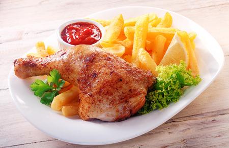 Close-up Gourmet Tasty Kippendij en frietjes op een witte plaat met sla, citroen en ketchup, geserveerd op een houten tafel. Stockfoto