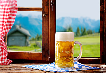 wooden window: Delicious refreshing tankard of ice cold Bavarian beer standing on a window sill in a rustic wooden tavern overlooking a view of the alps during the traditional Oktoberfest Stock Photo