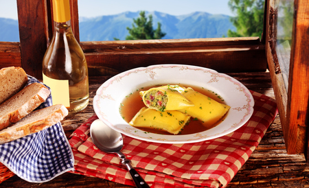 wiesn: German Ravioli with savory stuffing served with white wine and freshly baked bread on a rustic wooden windowsill with Alps view