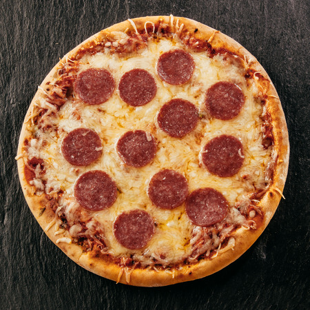 salami slices: Round homemade tasty pizza with crispy dough topped with mozzarella and salami slices Stock Photo
