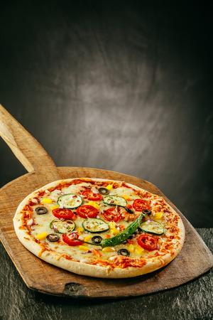 焼きたての蒸しスパイシーな唐辛子、トマト、ナス、オリーブと copyspace とレストランやピッツェリア木の板で役立たれてモッツァレラチーズをのせ