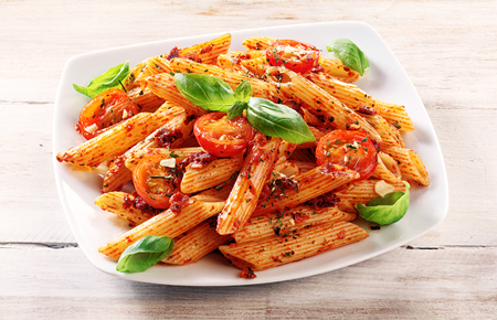 Close up Gourmet Tasty Spicy Italian Penne Pasta with Tomato and Herbs on a White Plate, Served on Top of a Wooden Table.