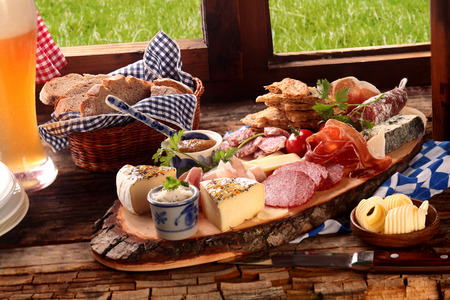 Delicious midday meal of a meat and cheese platter with a wide variety of cheeses, spicy sausage and ham served with a cold beer and fresh bread in a Bavarian tavern Imagens