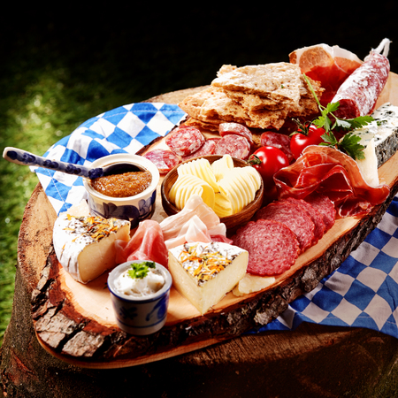 wiesn: Oktoberfest Meat and cheese platter with bread and an assortment of spicy sausages, ham and salami, on a rustic wooden board served outdoors in the garden on a checkered cloth
