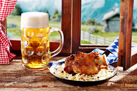 pub food: Roasted pork knuckle with crispy golden crackling on a bed of grated cheese served with a cold draft beer for a pub lunch at a Bavarian tavern during Oktoberfest with a view of the alps from a window