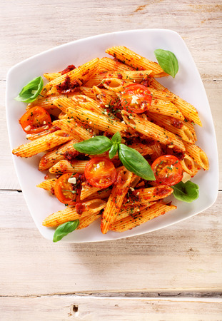 semolina pasta: Delicious Italian penne pasta with a spicy tomato sauce garnished with fresh basil leaves and sliced fresh tomatoes served on a plate Stock Photo
