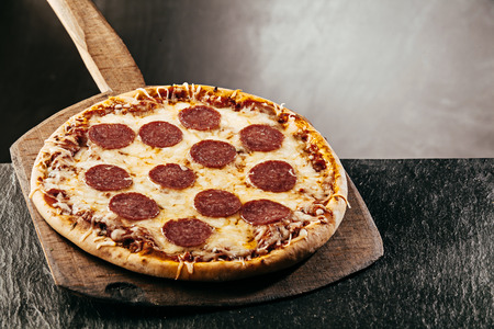 Appetizing Italian pepperoni pizza with sliced spicy salami sausage served whole on a wooden board
